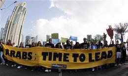 Ativistas levantam faixa durante marcha para exigir ações no combate à mudança climática em Doha, no Catar. Quase 200 países estenderam neste sábado o prazo para um fraco plano da Organização das Nações Unidas (ONU) para combater o aquecimento global até 2020, evitando um novo entrave a duas décadas de esforços da ONU que não foram capazes de impedir o aumento das emissões de gases do efeito estufa. 1/12/2012 REUTERS/Mohammed Dabbous