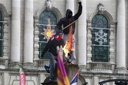 Protestors burn the Irish national flag in front of Belfast's City Hall December 8, 2012. REUTERS/Cathal McNaughton