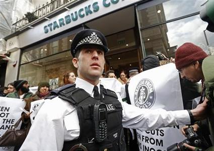 A police officer controls demonstrators outside a Starbucks coffee shop in central London December 8, 2012. Demonstrators from tax avoidance group UK Uncut, protested at Starbucks coffee shops across Britain on Saturday over the company's lack of corporate tax payments in Britain over the past three years. REUTERS/Luke MacGregor
