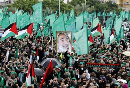 A picture depicting late Hamas founder Sheikh Ahmed Yassin (C) is seen as Palestinians take part in a rally marking the 25th anniversary of the founding of Hamas, in Gaza City December 8, 2012. REUTERS/Ahmed Jadallah