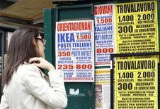 Immagine d'archivio di una ragazza davanti a locandine che pubblicizzano offerte di lavoro. REUTERS/Alessandro Garofalo (ITALY - Tags: BUSINESS EMPLOYMENT POLITICS)