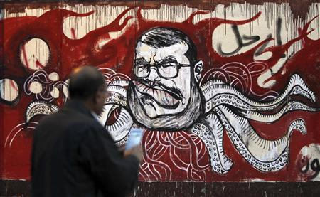A man take a picture of a mural of Egypt's President Mohamed Mursi and with Arabic words that reads ''Leave'' on the wall of the presidential palace in Cairo, December 8, 2012. REUTERS/Amr Abdallah Dalsh