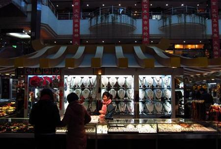 A woman serves customers at a jewellery stand at a shopping mall in central Beijing December 6, 2012. REUTERS/David Gray