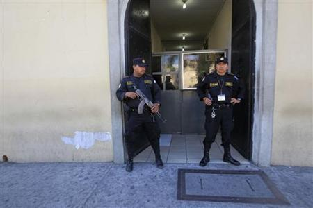 Two police officers stand guard at the entry of the Policia Nacional Civil hospital, where U.S. anti-virus software guru John McAfee receiving medical attention, in Guatemala City, December 6, 2012. REUTERS/Jorge Dan Lopez