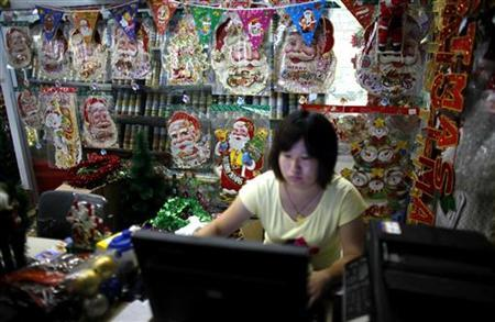 A woman works on a computer at a Christmas decoration shop in Yiwu, Zhejiang province September 13, 2012. REUTERS/Carlos Barria/Files