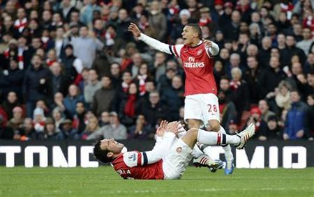 Arsenal's Santi Cazorla (bottom) reacts after winning a penalty following a challenge by West Bromwich Albion's Steven Reid during their English Premier League soccer match at the Emirates stadium in London December 8, 2012. REUTERS/Dylan Martinez