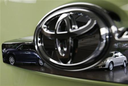 Toyota's Corolla Fielder (L) and Corolla Axio are reflected in a Toyota Forte's logo at the company's headquarters in Tokyo November 5, 2012. REUTERS/Kim Kyung-Hoon