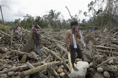 Residents search for their missing relatives among debris swept by floodwaters at the height of Typhoon Bopha, in New Bataan town in Compostela Valley, southern Philippines December 7, 2012. REUTERS/Erik De Castro