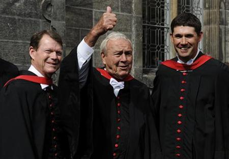 Veteran golfers Tom Watson (L) and Arnold Palmer (C) of the U.S pose with Padraig Harrington (R) of Ireland after they all received honorary degrees from the University of St Andrews, after a ceremony ahead of the British Open golf championship on the Old Course in St. Andrews, Scotland, July 13, 2010. REUTERS/Russell Cheyne/Files