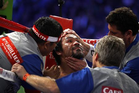 Manny Pacquiao of the Philippines is treated in his corner between rounds during his welterweight fight against Juan Manuel Marquez of Mexico at the MGM Grand Garden Arena in Las Vegas, Nevada December 8, 2012. Marquez sensationally knocked out Pacquiao in the sixth round of their non-title welterweight bout on Saturday, getting his first win over the Filipino in four attempts. REUTERS/Steve Marcus