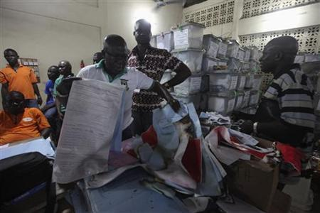 A man holds up damaged electoral documents at the Odorkor police station where ballot boxes from Ablekuma polling stations are stored, in Accra December 8, 2012. REUTERS/Luc Gnago