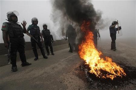 Police stand guard near tyres that activists of the Bangladesh Nationalist Party (BNP) set on fire during a nationwide blockade in Dhaka December 9, 2012. REUTERS/Andrew Biraj