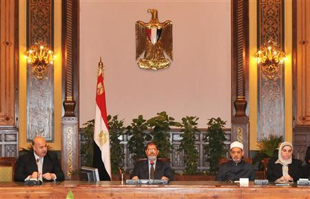 Egypt's President Mohamed Mursi (C) attends a meeting with Egypt's Vice President Mahmoud Mekky (L) with other politicians and heads of parties at the presidential palace in Cairo December 8, 2012. Mursi cancelled a decree which had sparked huge protests by giving him sweeping powers. REUTERS/Egyptian Presidency/Handout