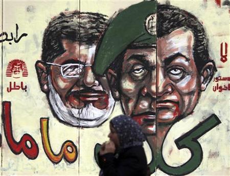 Anti-Mursi protester eats in front of graffiti with ( R to L ) Egypt's former president Hosni Mubarak, former Field Marshal Mohamed Hussein Tantawi and Egypt's President Mohamed Mursi on the wall of the presidential palace in Cairo, December 8, 2012. Mursi cancelled a decree which had sparked huge protests by giving him sweeping powers.The Arabic words read, ''No, the brotherhood's constitution, It's valid ''. REUTERS/Amr Abdallah Dalsh (EGYPT)