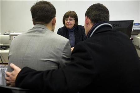 Candice Cathcart, (C) an administrative specialist with King County Elections assists Matt Beebe, (L) and David Mifflin as they filed for their marriage license in Seattle, Washington December 6, 2012. REUTERS/Jordan Stead