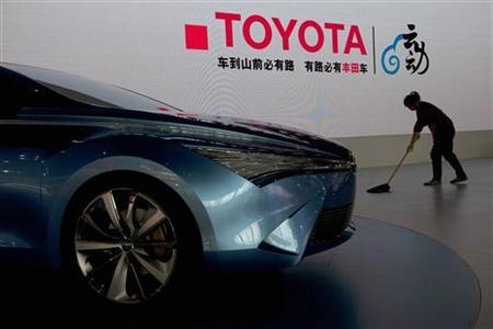 A worker cleans next to a Toyota NS4 plug-in hybrid concept car during the media preview of the 10th China International Automobile Exhibition in Guangzhou November 22, 2012. The auto show opens to the public from November 22 to December 2. REUTERS/Tyrone Siu (CHINA - Tags: TRANSPORT BUSINESS)