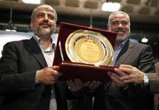 O líder do Hamas, Khaled Meshaal (esquerda), recebe uma escultura comemorativa, representando o que, segundo eles, é uma vitória sobre Israel, do líder sênior do Hamas, Ismail Haniyeh (direita), durante cerimônia na cidade de Gaza. 9/12/2012 REUTERS/Ahmed Jadallah