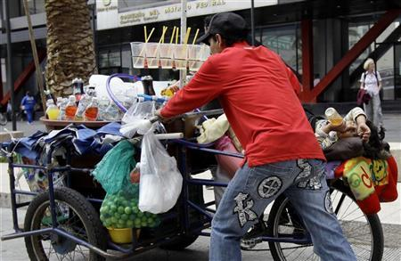 A street vendor selling soft drinks pushes his tricycle while his son lies on it on a street near the Zocalo main square in Mexico City July 31, 2012. REUTERS/Henry Romero