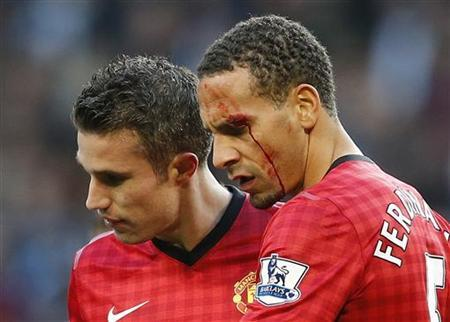 Manchester United's Rio Ferdinand (R) is helped from the pitch by teammate Robin van Persie after being struck by an object thrown from the crowd during their English Premier League soccer match against Manchester City at The Etihad Stadium in Manchester, northern England December 9, 2012. REUTERS/Phil Noble