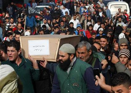 Lebanese Islamist gunmen and residents carry the coffin of one of their colleagues as three bodies arrived from Syria, in Tripoli in northern Lebanon December 9, 2012. Lebanese authorities received on Sunday the first three bodies from a group of 14 Lebanese and Palestinian gunmen killed in Syria, local clerics said, as fighting triggered by the men's death continued to shake the northern port town of Tripoli. REUTERS/ Fathi Al Masri