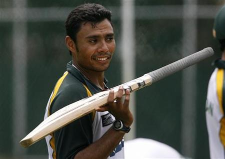 Pakistan's Danish Kaneria balances a bat on his fingers during a practice session in Colombo July 18, 2009. REUTERS/Vivek Prakash/Files