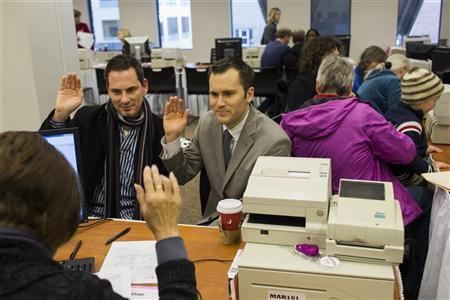 David Mifflin (L) and Matt Beebe swear an oath while filing for their marriage license in Seattle, Washington December 6, 2012. Washington made history last month as one of three U.S. states where marriage rights were extended to same-sex couples by popular vote, joining Maryland and Maine in passing ballot initiatives recognizing gay nuptials. REUTERS/Jordan Stead