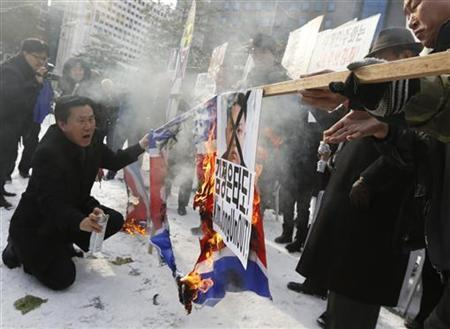 Anti-North Korean activists from conservative and right wing civic groups burn defaced North Korean flags and a portrait of the North's leader Kim Jong-Un during a rally denouncing the North's plan for rocket launch in Seoul December 6, 2012. REUTERS/Lee Jae-Won