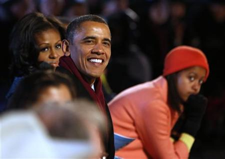 U.S. President Barack Obama (C) is joined by his daughter Malia (R) and first lady, Michelle Obama (L) as they watch the show at the official lighting of the National Christmas Tree ceremony on the Ellipse in Washington, December 6, 2012. REUTERS/Larry Downing