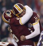 Washington Redskins place kicker Kai Forbath (R) is hugged by teammate Chris Chester (L) after Forbath kicked a game-winning field goal in overtime against the Baltimore Ravens in their NFL football game in Landover, Maryland December 9, 2012. REUTERS/Gary Cameron