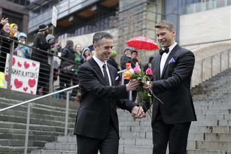 Seattle gay-rights advocate and journalist Dan Savage (L), and Terry Miller sort through roses on the steps of City Hall after getting married at Seattle City Hall in Seattle, Washington December 9, 2012. Washington made history last month as one of three U.S. states where marriage rights were extended to same-sex couples by popular vote, joining Maryland and Maine in passing ballot initiatives recognizing gay nuptials. REUTERS/Cliff Despeaux