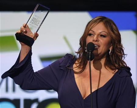 Mexican singer Jenni Rivera receives her award for top album by a woman performer at the 2009 Billboard Latin Music Awards in Miami, April 23, 2009. REUTERS/Carlos Barria/Files