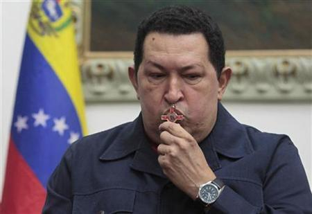 Venezuelan President Hugo Chavez kisses a crucifix as he speaks during a national broadcast at Miraflores Palace in Caracas December 8, 2012. REUTERS/Miraflores Palace/Handout