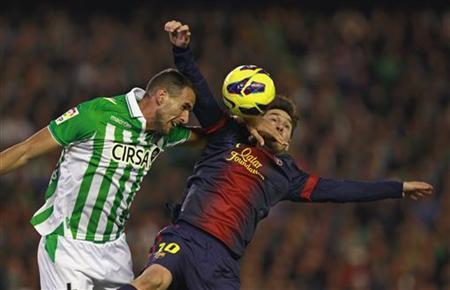 Barcelona's Lionel Messi (R) and Real Betis' Antonio Amaya jump for the ball during their Spanish First Division soccer match at Benito Villamarin Stadium in Seville December 9, 2012. REUTERS/Marcelo del Pozo