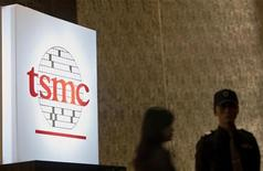 People stand behind a sign with a TSMC logo during TSMC's third quarter earnings conference in Taipei October 25, 2012. REUTERS/Yi-ting Chung