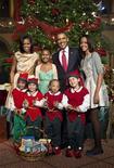 """El presidente de Estados Unidos, Barack Obama, se reunió el domingo con el legislador republicano y presidente de la Cámara de Representantes, John Boehner, en la Casa Blanca para negociar Modos para evitar el """"abismo fiscal"""", dijeron funcionarios de Gobierno y un asesor parlamentario. En la imagen, el presidente Barack Obama, la primera dama Michelle Obama, sus hijas Sasha (2ª I) and Malia, posan con unos niños antes del concierto de Navidad en el Museo Nacional de Washington, el 9 de diciembre de 2012. REUTERS/Joshua Roberts"""