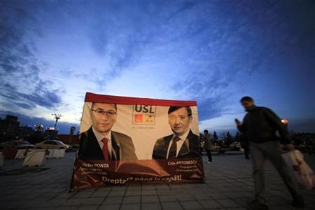 A man walks past an election poster showing Social Liberal Union (USL) leaders, leftist Prime Minister Victor Ponta, the president of Social Democrat Party and Crin Antonescu, the president of National Liberal Party (R), in downtown Bucharest December 3, 2012. REUTERS/Radu Sigheti