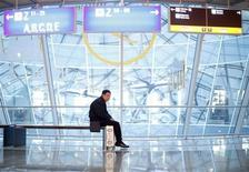 A man sits on a bench at the departure area at the Fraport airport in Frankfurt November 14, 2012. REUTERS/Lisi Niesner