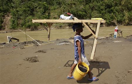 A Filipino small-scale miner carries his sand-sifting equipment used in gold mining on a river bed in the town of Mawab, Compostela Valley in southern Philippines December 9, 2012, five days after the year's strongest typhoon, Typhoon Bopha, first hit land. REUTERS/Erik De Castro
