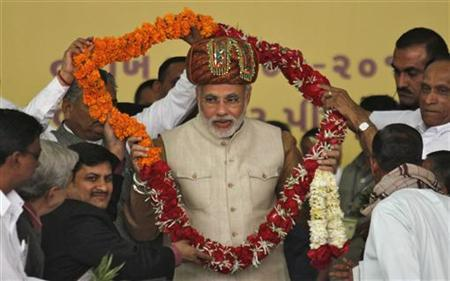 Gujarat's Chief Minister Narendra Modi (C) receives a garland from supporters during his day-long fast at Godhra in Gujarat January 20, 2012. REUTERS/Amit Dave/Files