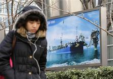 A woman walks past a poster showing an offshore work platform from the China National Offshore Oil Corp (CNOOC) next to its headquarters building in Beijing, December 10, 2012. CNOOC's promise of transparency, pledged to win approval from Canada for its $15.1 billion purchase of Nexen Inc, looks like a positive step on the face of it but is unlikely to represent a sea change in Chinese business practices. REUTERS/Jason Lee