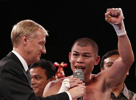 Chris John of Indonesia speaks to his Indonesian supporters after defeating Chonlatarn Piriyapinyo of Thailand during their WBA super world featherweight title fight at the Marina Bay Sands in Singapore early November 10, 2012. REUTERS/Edgar Su/Files