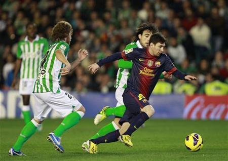 Barcelona's Lionel Messi (R) is challenged by Real Betis' players during their Spanish First Division soccer match at Benito Villamarin stadium in Seville December 9, 2012. REUTERS/Marcelo del Pozo