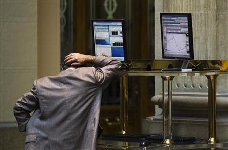 A trader reacts after looking at computer screens at Madrid's bourse August 2, 2012. REUTERS/Susana Vera/Files