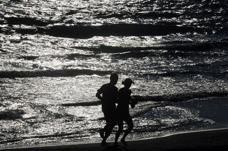 Foreign tourists jog on a beach in Zacharo town some 320 kms southwest of Athens May 30, 2012. REUTERS/Yannis Behrakis