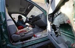 Policial afegão inspeciona interior do carro que pertencia ao chefe de polícia da província de Nimroz, que foi atingido por uma bomba, na província de Herat, no Afeganistão. 10/12/2012 REUTERS/ Mohammad Shoib