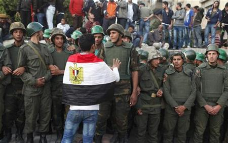 An anti-Mursi protester with an Egyptian flag around his shoulders talks to soldiers standing guard outside the Egyptian presidential palace in Cairo December 9, 2012. REUTERS/Asmaa Waguih
