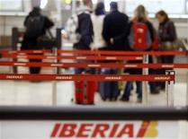 Los aeropuertos españoles registraron en noviembre un nuevo descenso en operaciones y pasajeros, según datos publicados el lunes por el gestor público aeroportuario Aena. En la imagen, clientes hacen cola en un mostrador de Iberia, en el aeropuerto de Madrid-Barajas, el 9 de noviembre de 2012. REUTERS/Sergio Pérez