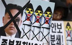 """Плакаты участников акции протеста против северокорейского пуска ракеты в Сеуле 6 декабря 2012 года. Северная Корея отодвинула крайний срок осуждаемого соседями и Западом запуска ракеты дальнего радиуса действия на неделю, обнаружив """"технические неисправности"""", сообщило госинформагентство КНДР в понедельник. REUTERS/Lee Jae-Won"""