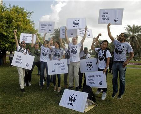Activists pose for a picture before a march to demand action to address climate change in Doha December 1, 2012. REUTERS/Mohammed Dabbous