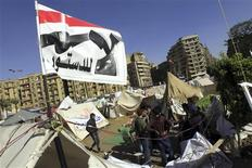 "Anti-Mursi protesters sit outside their tents, below a flag that reads, ""No, to Constitution"" at Tahrir Square in Cairo December 10, 2012. REUTERS/Mohamed Abd El Ghany"